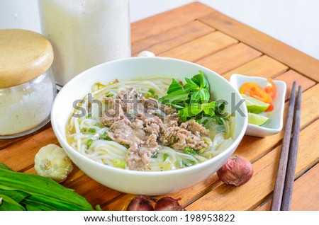 Beef meat rice noodle pho soup on wooden table - stock photo
