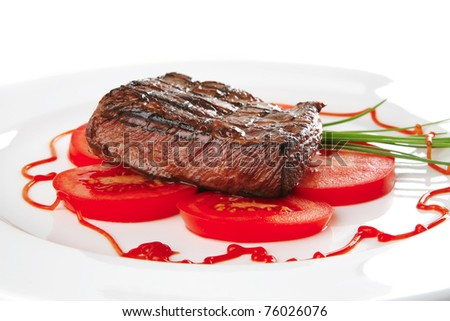 beef meat served on white plate with tomato - stock photo