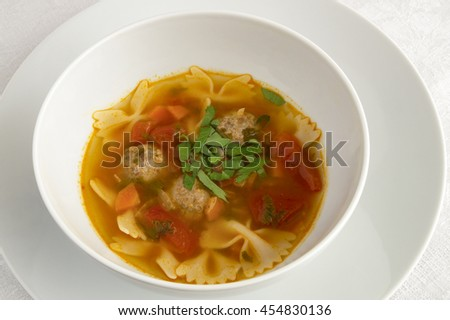 beef meatball soup with farfalle pasta decorated by parsley - stock photo