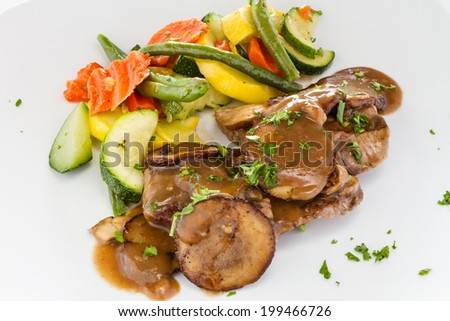 Beef medallions with mushroom sauce and vegetable medley. - stock photo