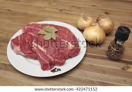 Beef on a plate with a few onions and  four seasons pepper - stock photo