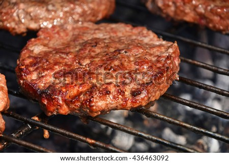Beef or pork meat barbecue burgers for hamburger prepared grilled on bbq smoke grill, close up
