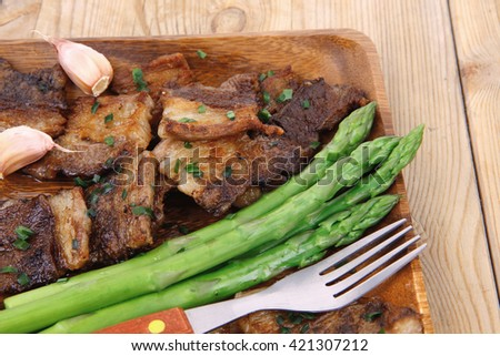 beef pork meat grilled ribs with asparagus and garlic over wooden background table - stock photo