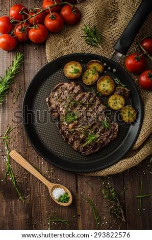 Beef rib eye steak with rustic potatoes, fresh herbs and tomatoes, sprinkled sea salt and herbs - stock photo