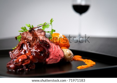 Beef roast with shallot and mushroom wine gravy and side of salt crusted potatoes with red mojo sauce - stock photo