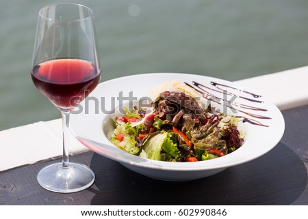 beef salad serve by the river with red wine