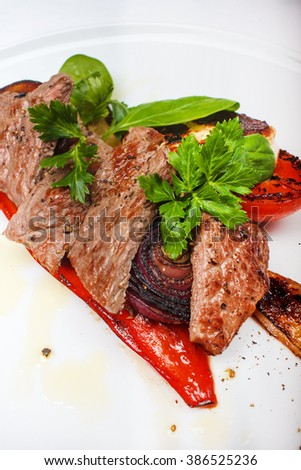 Beef sirloin with grilled vegetables and homemade grilled cheese on white board - stock photo