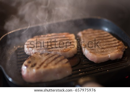 Beef steak fry in a frying pan in smoke and steam.