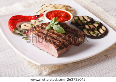 beef steak, grilled vegetables and sauce on a plate close-up. horizontal   - stock photo