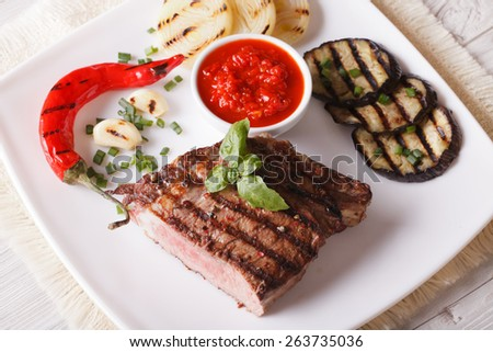 beef steak, grilled vegetables and sauce on a plate close-up. horizontal view from above  - stock photo
