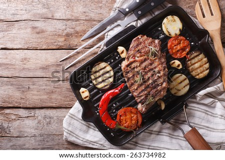 beef steak grilled with onions and eggplant in the pan grill. horizontal view from above  - stock photo