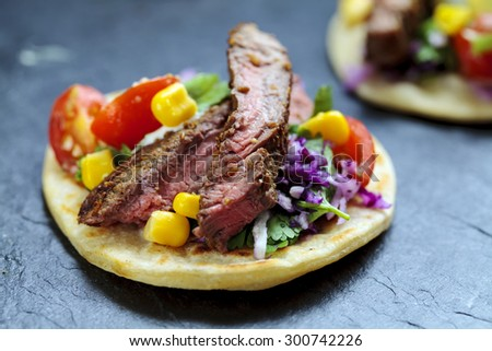 Beef steak tortillas with sweet corn, avocado and tomato salsa and red cabbage coleslaw - stock photo