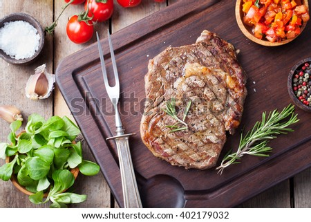 Beef steak with cherry tomato and rosemary on a dark cutting board Wooden background Top view Copy space - stock photo