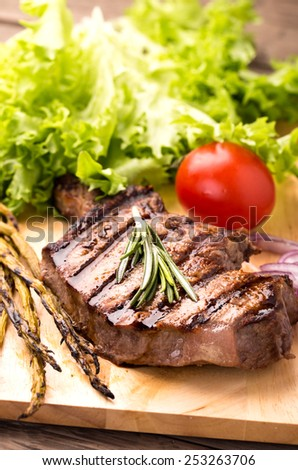 Beef steak with fresh herbs and tomatoes on wooden plate vertical