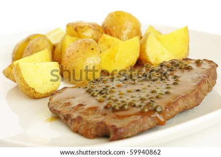 Beef steak with green pepper and baked potatoes - stock photo