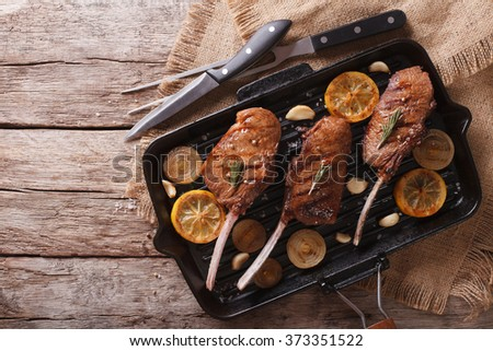 Beef steak with lemon on a grill pan on the table. horizontal top view - stock photo