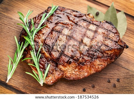 Beef steak with rosemary on a wooden table. - stock photo