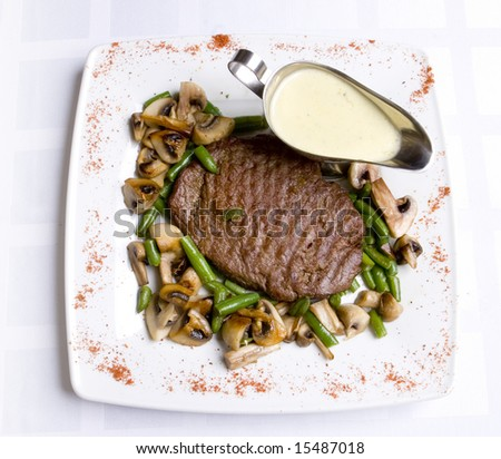 Beef steak with sauce,  roasted green bean and mushrooms  on white plate