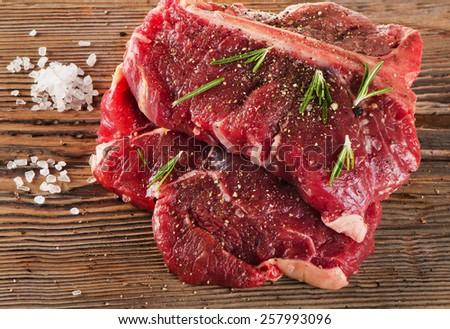 Beef Steak with Seasoning and fresh herbs on  wooden board. Selective focus - stock photo