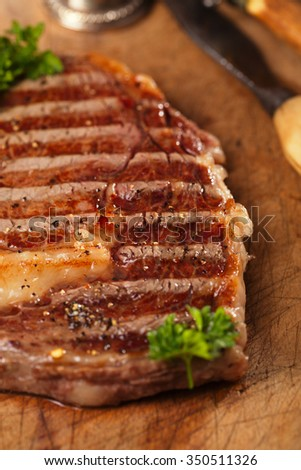 beef steak with vintage meat fork  on old wooden background