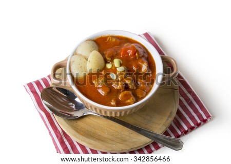 Beef stew in bowl with tomato sauce on a napkin red and white striped background - stock photo