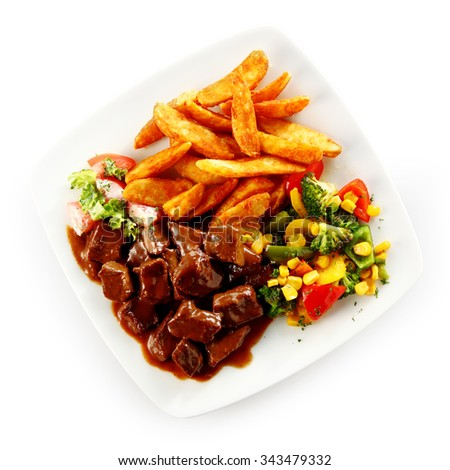 Beef stew or goulash in a delicious rich brown gravy with mixed vegetables and fried potato chips viewed high angle on a white plate over a white background - stock photo