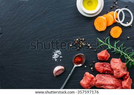Beef stew raw ingredients on black slate top view - stock photo