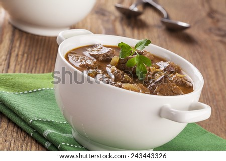 Beef stew served with bread in a plate on a wooden background - stock photo