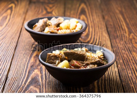 Beef stew with noodles and potatoes in ceramic bowl on wooden table - stock photo