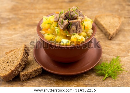 Beef stew with potatoes in ceramic bowl over rustic wooden background - stock photo