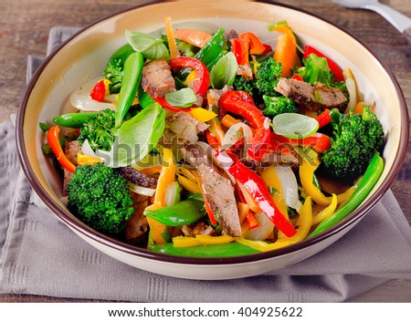 Beef stir fry with vegetables on  wooden table. Healthy eating.