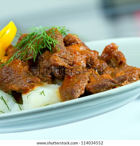 Beef stroganoff over boiled potatoes with pepper and dill - stock photo