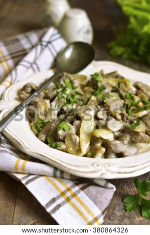 Beef stroganoff with mushrooms in a vintage plate. - stock photo