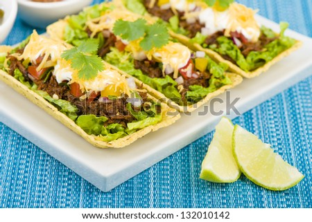 Beef Tacos - Shredded beef taco trays topped with salsa, sour cream and grated cheese. - stock photo