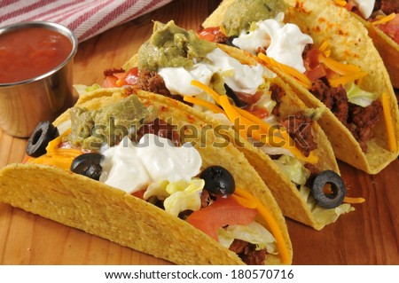 Beef tacos with lettuce, tomato, black olive, cheddar cheese, guacamole and sour cream - stock photo