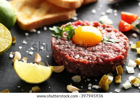 Beef tartare with egg yolk on a black wooden table - stock photo