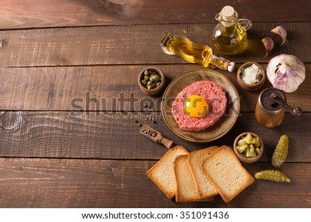 Beef tartare with pickled cucumber and fresh onions on dark wooden background