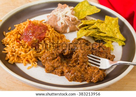 Beef tips in highly seasoned sauce is  Carne Guisada, heart of this Mexican Dinner with rice and beans and spicy jalapeno tortilla chips. - stock photo