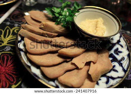Beef tongue as appetizer in the uzbek restaurant - stock photo