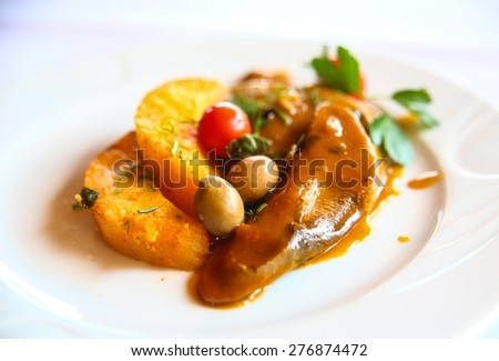 Beef tongue with potato and olives in sauce - stock photo