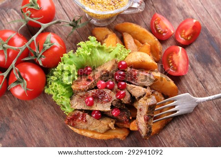 Beef with cranberry sauce, roasted potato slices and bun on cutting board, on wooden background - stock photo