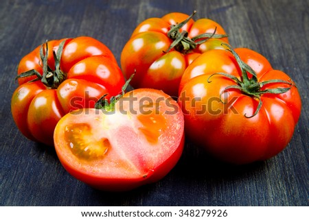 Beefsteak tomatoes, isolated on wood - stock photo