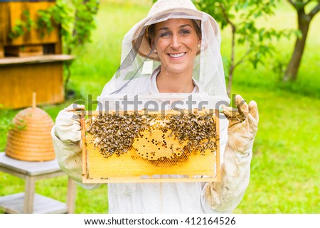 Beekeeper controlling beehive and comb frame  - stock photo