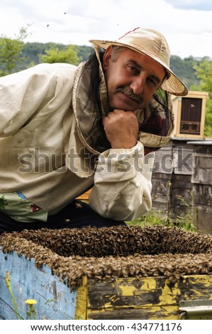 Beekeeper with the honey frame on the apiary