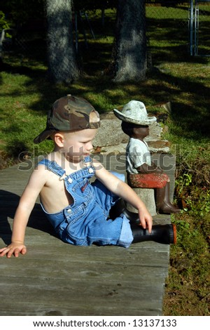 Been fishing long?  Small child sits besides statue of little black boy that is fishing off pier.  Child has on overalls, hat and black rubber boots. - stock photo