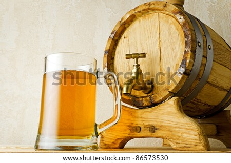 Beer and barrel on the wood table. - stock photo