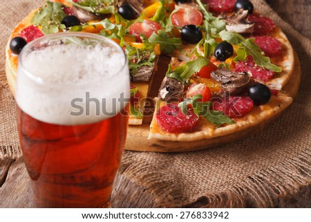 Beer and hot pizza with arugula on the table close-up horizontal. rustic style  - stock photo