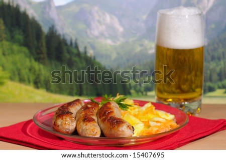 Beer and sausages against mountains - stock photo