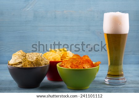 Beer and various types of chips - stock photo