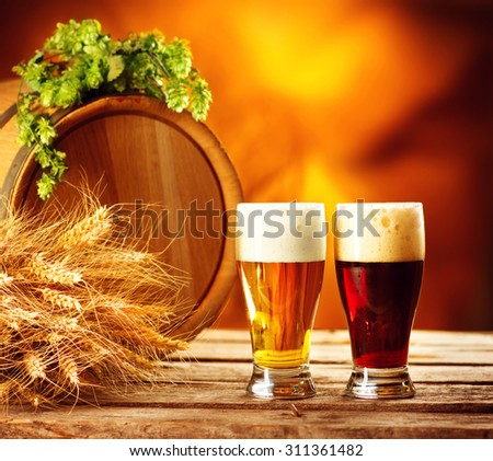 Beer barrel and two beer glasses with green hop and ears of wheat on wooden table. Dark and light beer. Brewery concept. Brewing traditions - stock photo